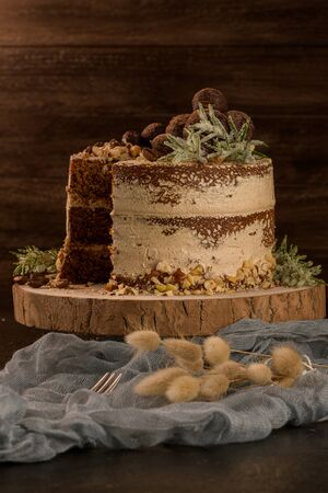 Slice of delicious naked coffee and hazelnuts cake on table rustic wood kitchen countertop. Standard-Bild - 134846065