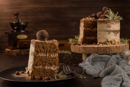 Slice of delicious naked coffee and hazelnuts cake on table rustic wood kitchen countertop. Standard-Bild - 134846049