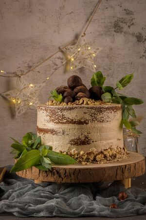 Delicious naked coffee and hazelnuts cake on table rustic wood kitchen countertop. Standard-Bild - 134846051