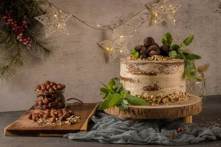 Delicious naked coffee and hazelnuts cake on table rustic wood kitchen countertop. Standard-Bild - 134846041