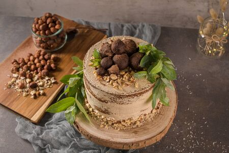 Delicious naked coffee and hazelnuts cake on table rustic wood kitchen countertop. Standard-Bild - 134846043