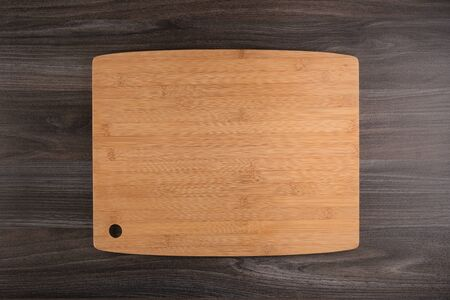 Top view of wooden cutting board on old dark wood countertop. Banque d'images