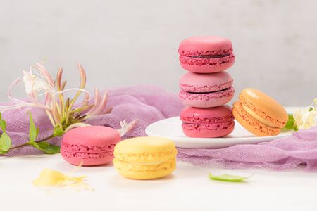 A french sweet delicacy, macaroons variety closeup. Color fresh macarroons on wooden bacground