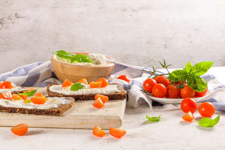 Rye bread bruschetta with cream cheese, olive oil and basil dip, cherry tomatoes, fresh basil leaves on wooden board.