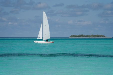 catamaran: Sailing catamaran on the ocean. Island in the background Stock Photo