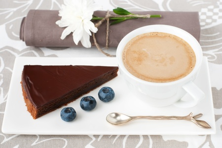 Chocolate tart with bilberry and a cup of coffee on a cute table appointments photo