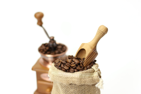 Fresh coffee beans in a bag with Coffee grinder on white background