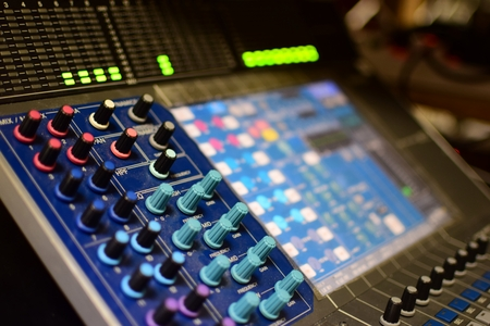 decibel: Shallow Depth-of-field Generic Photo of Concert Music Broadcast Soundboard Mixer and Equalizer with Knobs and Audio Volume Indicator Lights