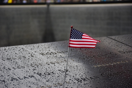 Memorial at Ground Zero Manhattan for September 11 Terrorist Attack with an American Flag Standing near the Names of Victims Engraved Editorial