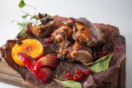 Grilled duck with apple, red berries, orange and red pear on wooden board. Stock Photo