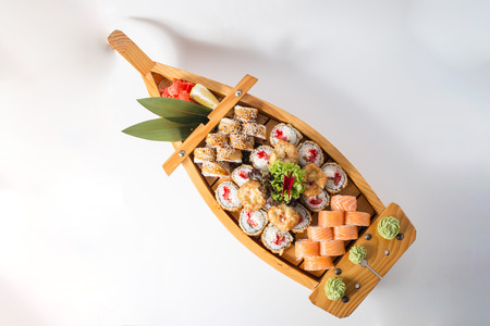 Wooden boat with lots of sushi with ginger and wasabi. Banco de Imagens