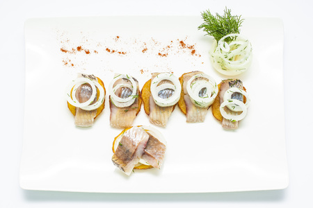 Salted herring with crackers, onion, green and paprika on white plate.