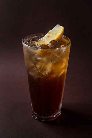 Glass of ice tea with ice and slice of lemon on elegant dark brown background.