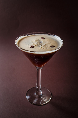 Glass of espresso martini with coffee beans and vodka on elegant dark brown background.