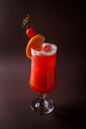 Glass of red alcohol cocktail with cherry and slice of orange on elegant dark brown background. Imagens