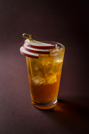 Glass of whisky cocktail with slices of apple on elegant dark brown background.