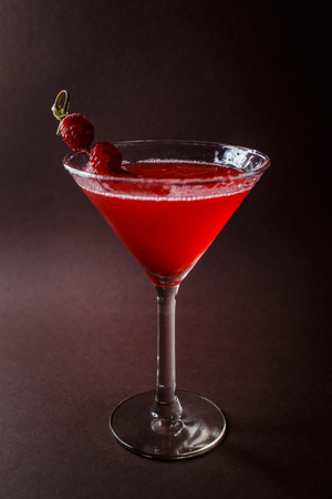 Glass of red cocktail with paspberries on elegant dark brown background.