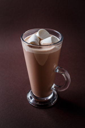 Glass of cacao with three marshmallows on elegant dark brown background.