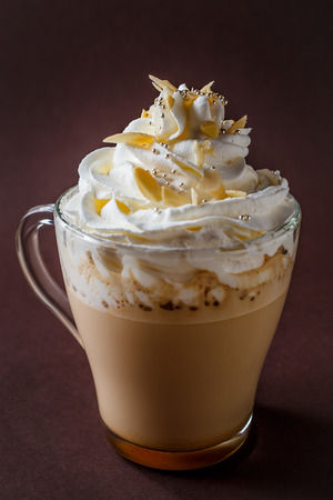 Glass of coffee with whipped cream and almonds shaving on elegant dark brown background. 写真素材