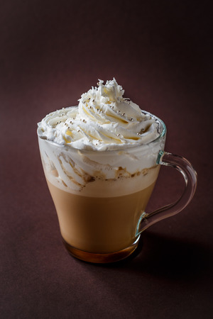 Glass of coffee with whipped cream on elegant dark brown background.