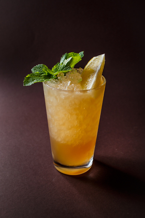 Glass of orange cocktail with mint, ice and slice of orange on elegant dark brown background.