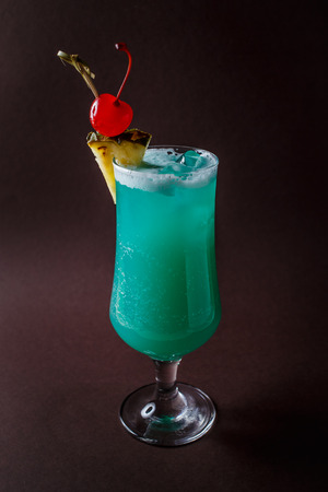 Glass of blue coctail with cherry and slice of pineapple on elegant dark brown background.