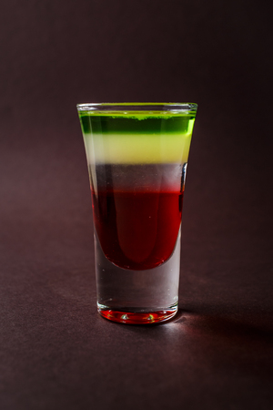 Alcoholic shot glass with grenadine, absent on elegant dark brown background.