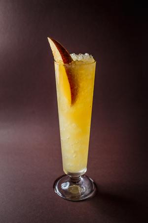 Glass of rum with orange, lime, pineapple juice and piece of mango on elegant dark brown background. 写真素材