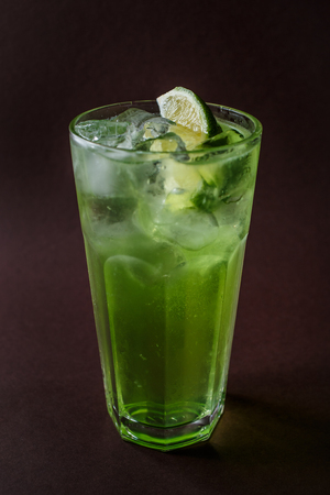 Glass of mojito with ice and slice of lime on elegant dark brown background. 写真素材