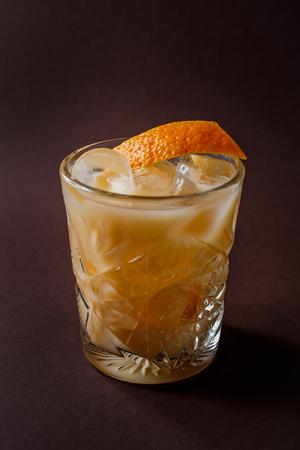Glass of orange alcohol cocktail with ice and slice of orange on elegant dark brown background.