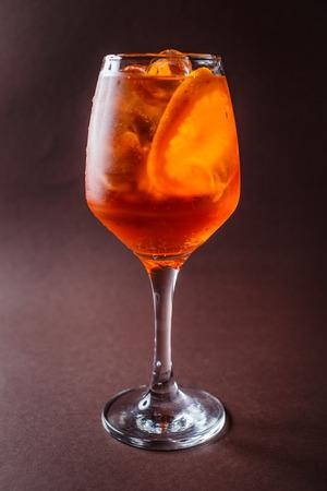Glass of Aperol Spritz with orange on elegant dark brown background.