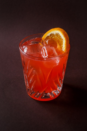 Glass of red alcohol cocktail with ice and slice of orange on elegant dark brown background.