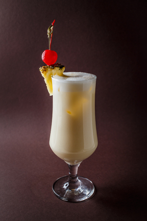 Glass of pina colada with berry and pineapple on elegant dark brown background.