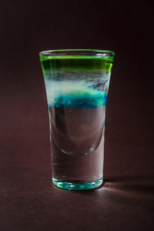 Clouds Alcoholic shot glass with absent, sambuca, tequila, blue curacao on elegant dark brown background.