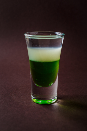 Green mexican alcoholic shot glass with tequila on elegant dark brown background.