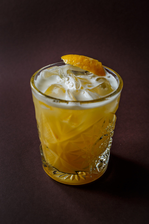 Glass of yellow alcohol cocktail with ice and slice of lemon on elegant dark brown background. 写真素材