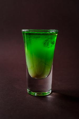 Green alcoholic shot glass with absent, irish cream, liquor on elegant dark brown background.