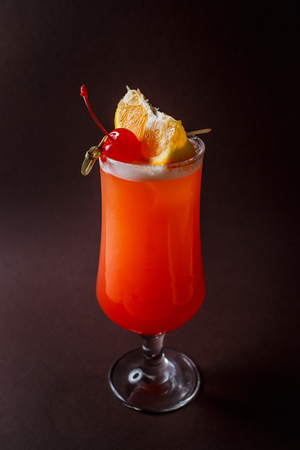 Glass of red alcohol cocktail with cherry and slice of orange on elegant dark brown background. 写真素材