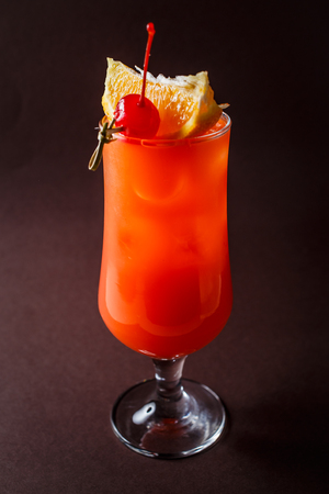 Glass of red alcohol cocktail with cherry, slice of orange and straw on elegant dark brown background.