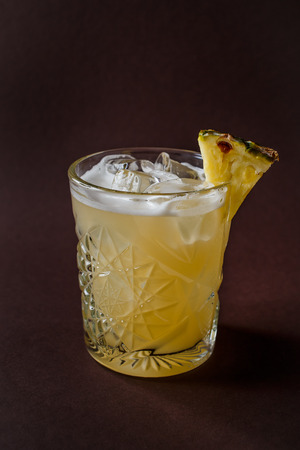 Glass of yellow alcohol cocktail with ice and slice of pineapple on elegant dark brown background.