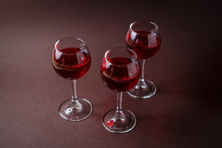 3 small glasses of red liquor on elegant dark brown background. 写真素材