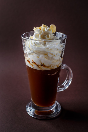 Glass of frappucino with whipped cream and almonds shaving on elegant dark brown background. 写真素材