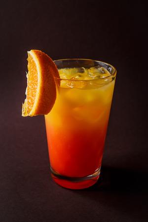 Glass of orange coctail with ice and slice of orange on elegant dark brown background.