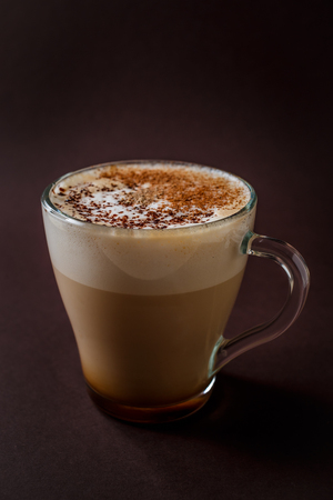Glass of coffee with chocolate topping on elegant dark brown background. 写真素材