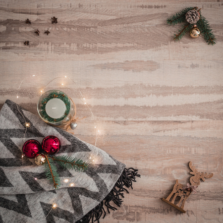 Seasonal Christmas border composed of decorative gifts, deer, candle and scarf, pine branches ornaments over a wooden background with copyspace, overhead view.