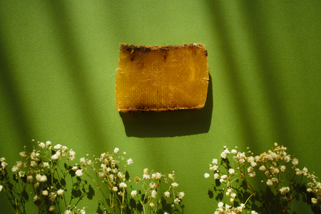Natural eco soap and field flowers on green background with shadows.