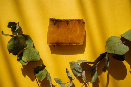 Natural eco soap and green leaves on yellow background with shadows.