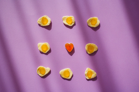 Candy jelly eggs and heart on violet background with shadows. Unique surrealism. Sweets. Marmelade.