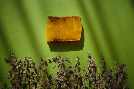 Natural eco soap and lavender flowers on green background with shadows.