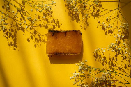 Natural eco soap and field flowers on yellow background with shadows.